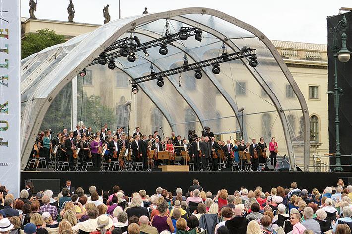 Bühne mit Rundbogendach, darauf Daniel Barenboim und die Staatskapelle.