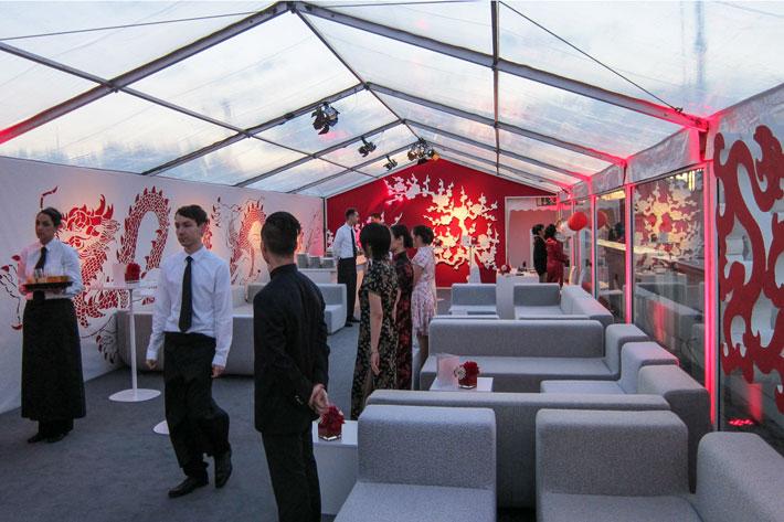 Zeltinnere bei Tag mit Sitzgelegenheiten und Bedienpersonal, Dekoration in chinesischem Stil