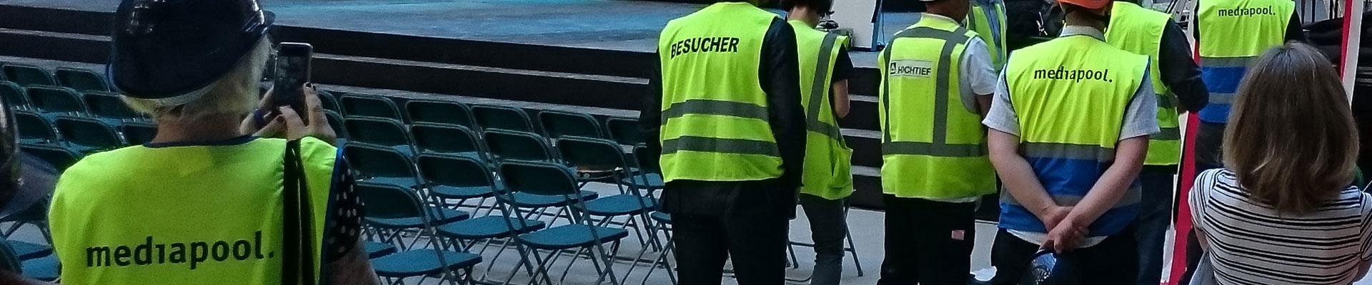 Rückenansicht von mediapool-MitarbeiterInnen mit neongrünen Schutzwesten.