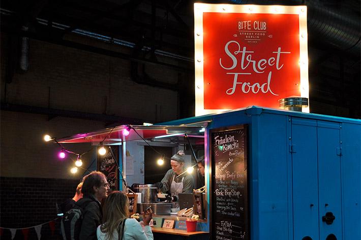 Berlin Travel Festival 2018: der Streetfoodstand von Fräulein Kimchi mit roter Streetfood-Leuchtreklame und Gästen.