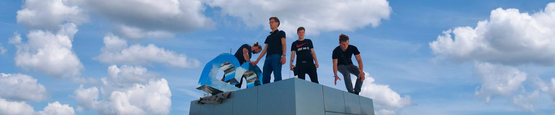 Vier mediapool-Mitarbeiter montieren ein dekorationselement, im Hintergrund ein blauer Wolkenhimmel.