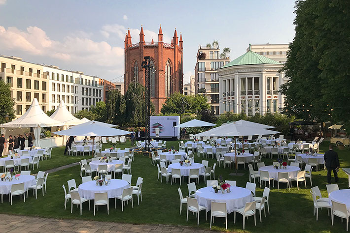 Parlamentarischer Abend der BIMA 2019: Der Garten des Kronprinzenpalais mit Tischen Bühne und Zelten vor Veranstaltungsbeginn.