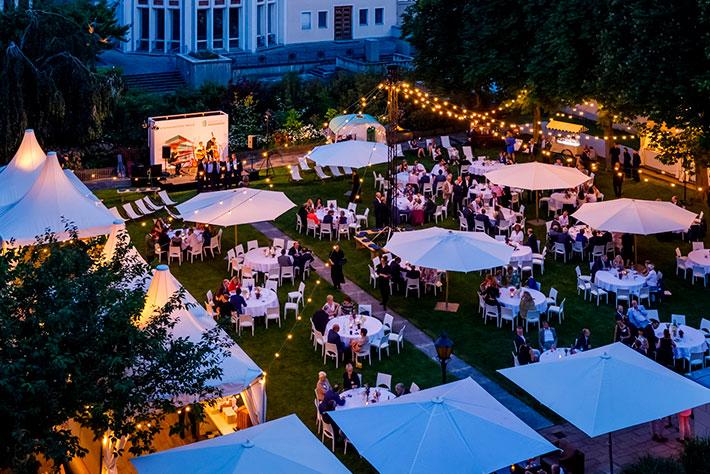 Parlamentarischer Abend der BIMA 2019: Der Garten des Kronprinzenpalais mit Tischen, Bühne und Zelten während der Veranstaltung.