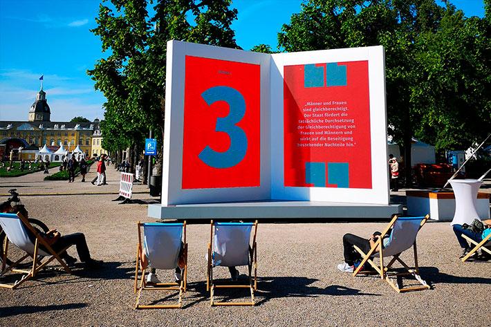 Informationstour 70 Jahre Grundgesetz: TourbesucherInnen in Liegestühlen vor der Buch-Installation.