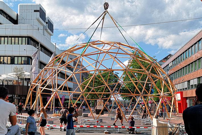 Evangelischer Kirchentag 2019: Die Skelett-Konstruktion des Kuppelzeltes hängt während des Aufbaus an einem Kranhaken.