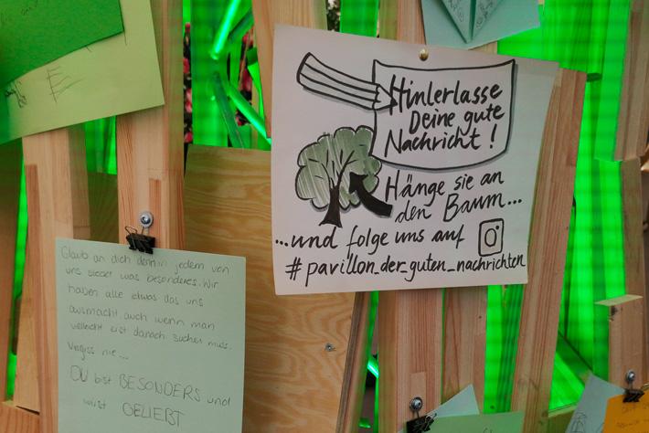 """Evangelischer Kirchentag 2019: Ein Zettel am """"Baum der Guten Nachrichten"""" verweist auf den Hashtag #pavillon-der-guten-nachrichten."""