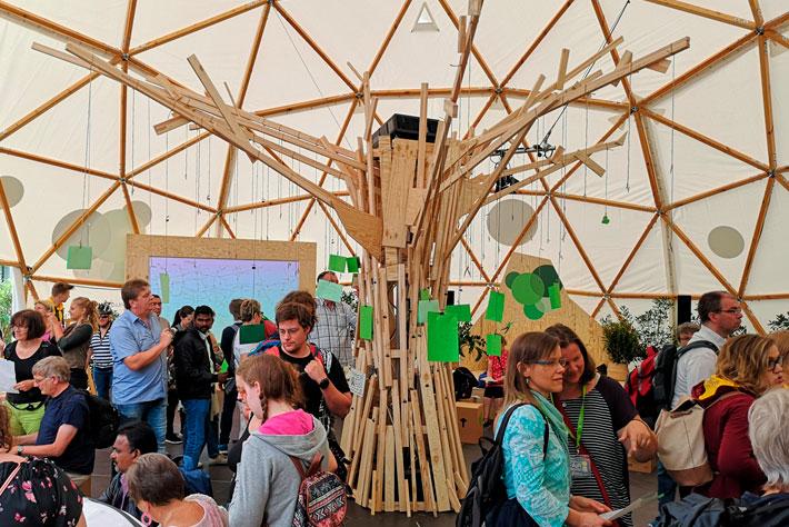 """Evangelischer Kirchentag 2019: Innenansicht des Kuppelzeltes mit Besucherinnen. Im Mittelpunkt der """"Baum der guten Nachrichten""""."""