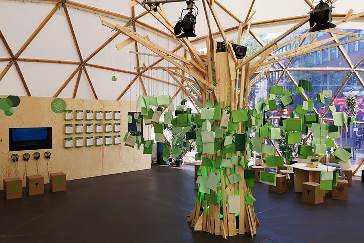 """Evangelischer Kirchentag 2019: Innenansicht des Pavillons ohne Besucherinnen mit dem """"Baum der guten Nachrichten"""", Medienwand, Tischen und Hockern."""