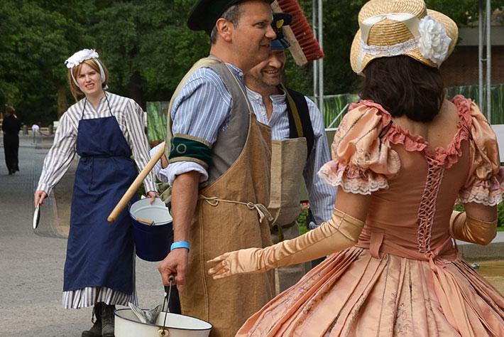 175 Jahre Zoo Berlin: Zoowärter in historischen Kostümen unterhalten sich mit einer Darstellerin in einem Biedermeierkostüm.