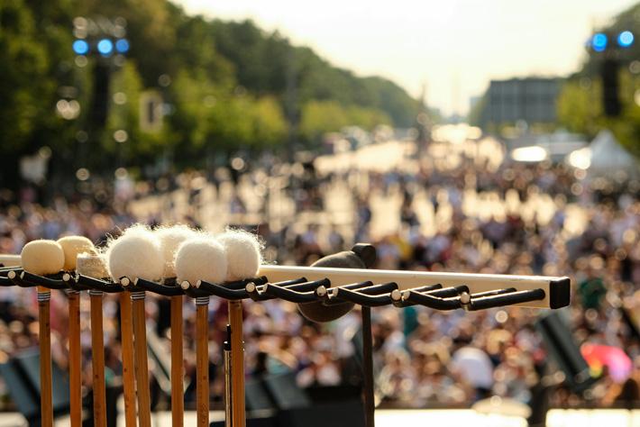 Die Berliner Philharmoniker am Brandenburger Tor: Blick auf die Klöppel des Orchester Schlagzeugers, im Hintergrund verschwommen das Publikum.
