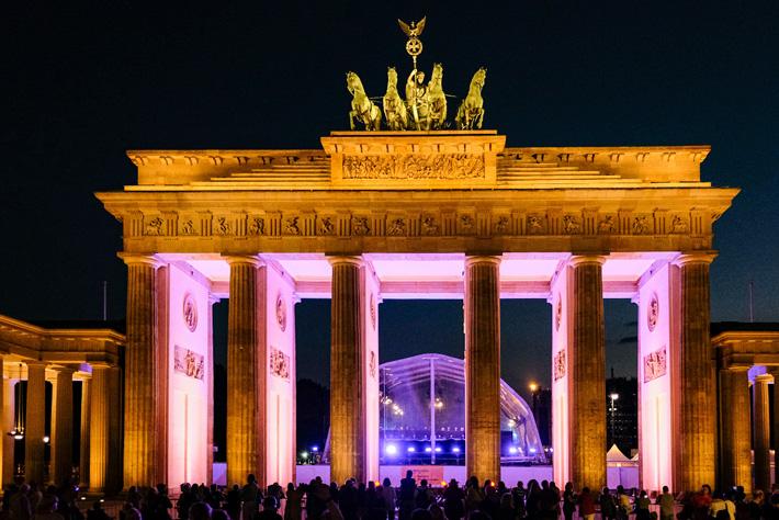 Die Berliner Philharmoniker am Brandenburger Tor: Blick durch das goldfarben beleuchtete Brandenburger Tor mit imposanter Quadriga auf die Rückansicht der Konzertbühne.