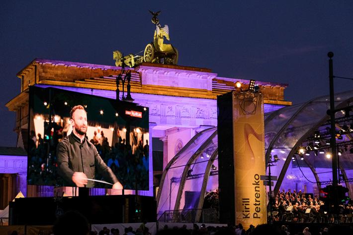 Die Berliner Philharmoniker am Brandenburger Tor: Chefdirigent Kirill Petrenko auf dem Großbild LED-Screen während des Konzerts.