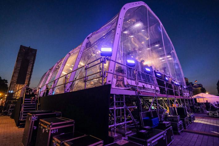 Die Berliner Philharmoniker am Brandenburger Tor: Rückansicht des Bühnenaufbaus mit Zelt und Monitorturm vor abendlichem Himmel.
