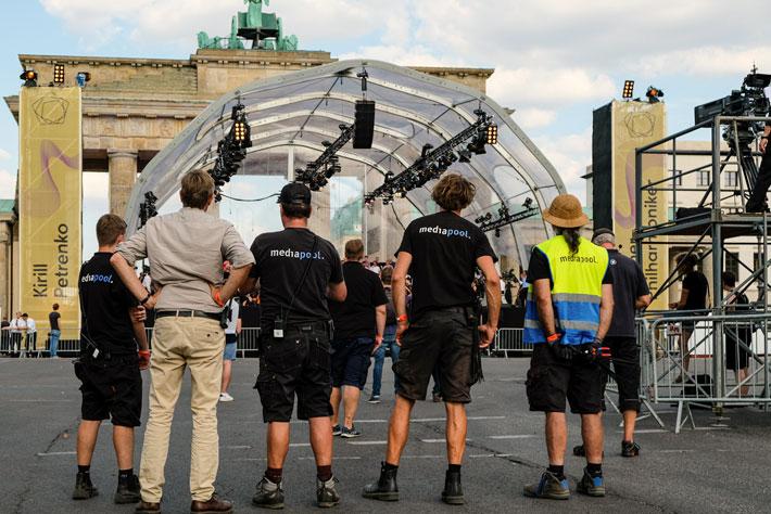 Die Berliner Philharmoniker am Brandenburger Tor: Rückansicht von mediapool-Mitarbeitern während des Veranstaltungsaufbaus vor dem Bühnenzelt und dem Brandenburger Tor.