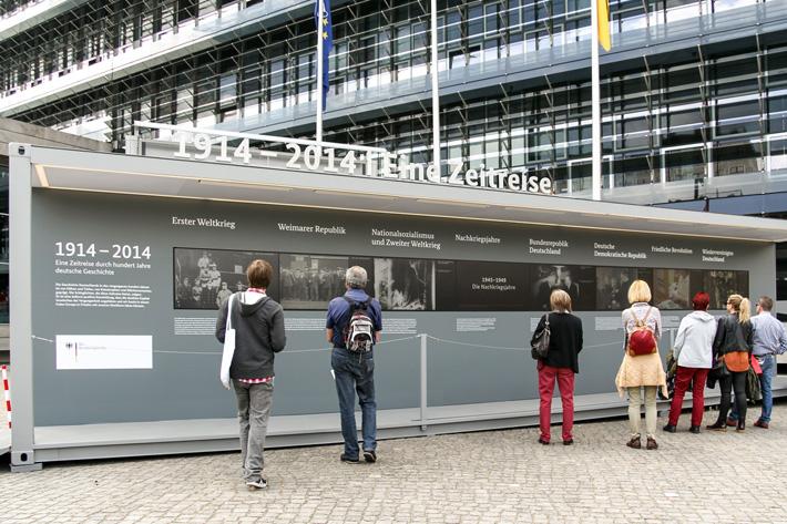 Ausstellungsmodul mit 8 Monitoren vor dem Bundespresseamt mit Betrachterinnen