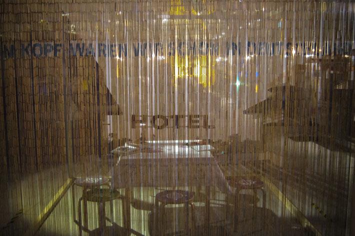 Durch den Bambusvorhand Titel der Ausstellung, Hocker und Tisch sichtbar