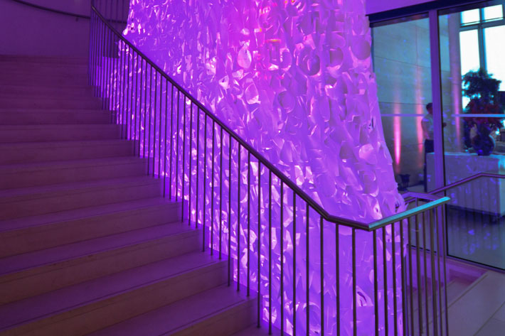 Treppenaufgang im Haus, im Inneren abgehängter, marmorierter Stoff mit lila Licht ausgeleuchtet.