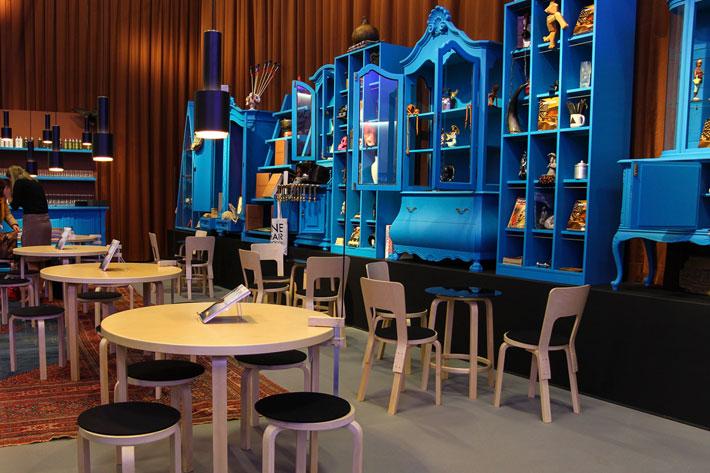 seitlicher Blick auf die alten, blauen Möbel, davor Stühle, Hocker und Tische