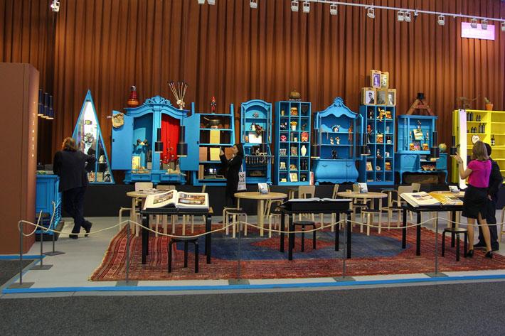 Stand mit altem Teppich und alten, blau bemalten, Möbeln
