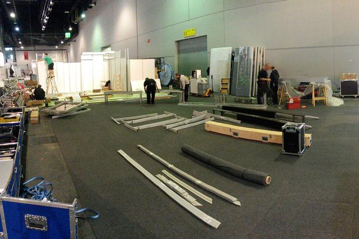 vor dem Aufbau der Messestände liegt diverses Material auf grauem Teppichboden