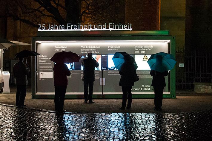 Besucherinnen mit Regenschirmen am Abend vor den Monitoren des Informationscontainers.
