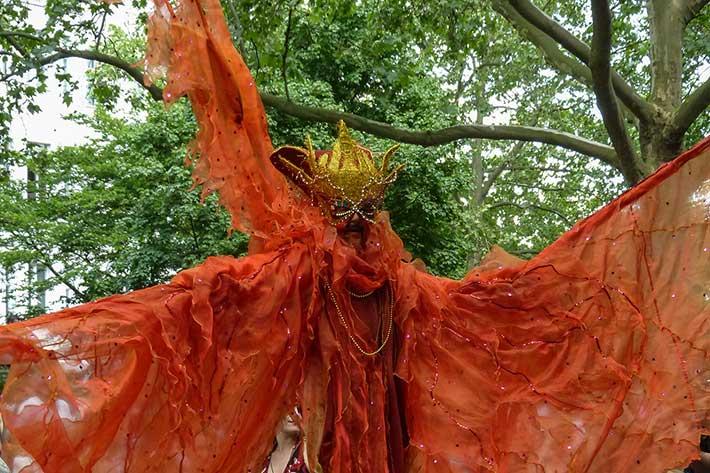 Stelzenfigur in orange mit großen Schwingen