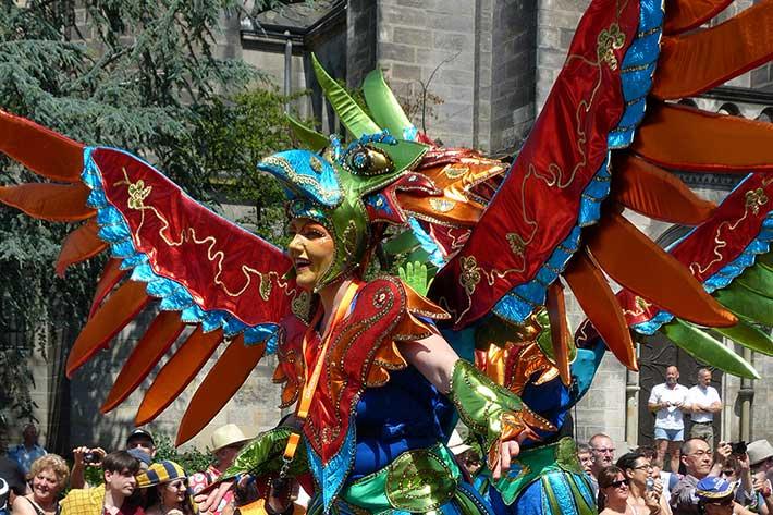Frau als Vogel mit großen roten Schwingen verkleidet