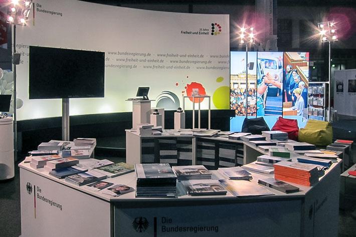 Leipziger Buchmesse: im Vordergrund octagonförmiger Tresen mit Broschüren und Flyermaterial, im Hintergrund angeleuchtete halbrunde Rückwand des Messestande