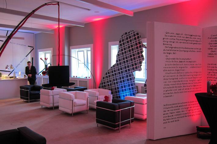 Mit Ledersesseln in weiß und schwarz ausgestatteter Raum, Trennwand mit Texten, vor einem Fenster die Silhouette eines Männerkopfes