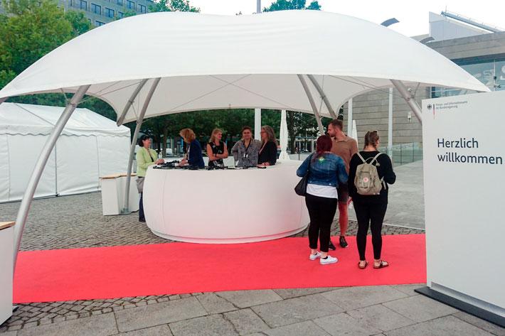 Tag der offenen Tür im Bundespresseamt 2017: Infocounter auf dem Vorplatz mit rotem Teppich und Gästen.