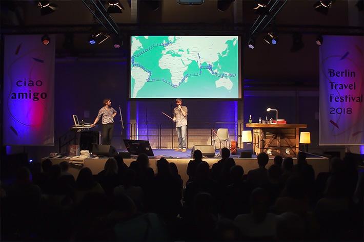 Berlin Travel Festival 2018: Bühnensituation während eines Vortrages mit Speaker, Projektion und Publikum.