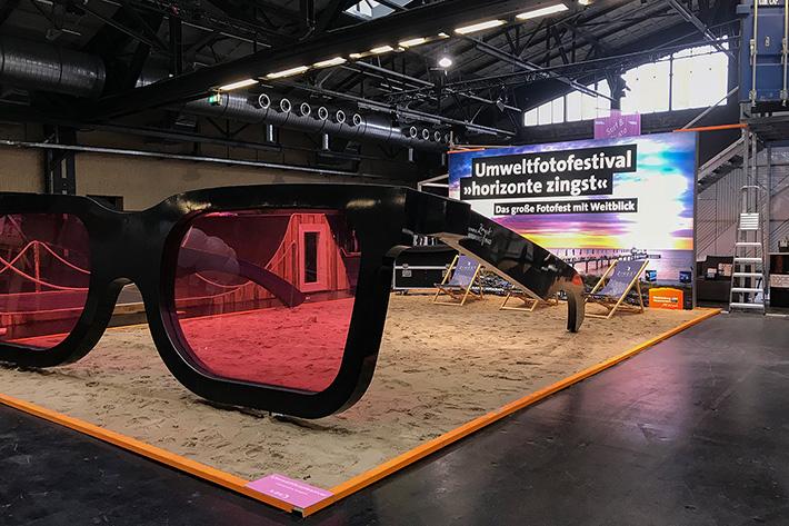 Berlin Travel Festival 2018: Stand des Umweltfotofestivals in Zingst mit riesenhafter Brille und Liegestühlen auf Sandoberfläche.